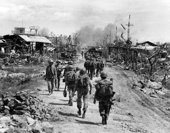 A line of South Vietnamese troops move along a devastated street in Quang Tri City as the battle continues for the provincial capital on July 28, 1972. Government forces were the midst of a campaign to retake the northern South Vietnamese city which was captured by enemy forces two months earlier. (AP Photo)