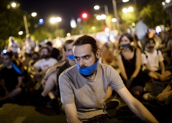 """Demonstrators cover they mouth with a gag as they sit on the street called by """"Rodea el Congreso"""" (Surround the Parliament) platform during a fake assault to the lower house of Spanish Parliament to protest against the public security law """"ley mordaza"""" (gag law), in Madrid on late June 30, 2015. The lower house of parliament approved on December 12, 2014 the law  -dubbed the """"Ley Mordaza"""" or """"Gag Law"""" by its critics-  which introduces hefty fines for unauthorised protests and allows for the summary expulsion of migrants that try to enter the country illegally, has sparked fierce opposition from human rights activists. AFP PHOTO / DANI POZO"""