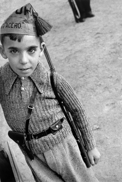 """SPAIN. Barcelona. August-September 1936. The boy is wearing a cap belonging to a member of the Steel Battalions, of the """"Union de Hermans Proletarios"""" (Union of Proletarian Brothers), an anarchist militia. Contact email: New York : photography@magnumphotos.com Paris : magnum@magnumphotos.fr London : magnum@magnumphotos.co.uk Tokyo : tokyo@magnumphotos.co.jp Contact phones: New York : +1 212 929 6000 Paris: + 33 1 53 42 50 00 London: + 44 20 7490 1771 Tokyo: + 81 3 3219 0771 Image URL: http://www.magnumphotos.com/Archive/C.aspx?VP=Mod_ViewBoxInsertion.ViewBoxInsertion_VPage&R=2S5RYD17S4ZX&RP=Mod_ViewBox.ViewBoxZoom_VPage&CT=Image&SP=Image&IT=ImageZoom01&DTTM=Image&SAKL=T"""
