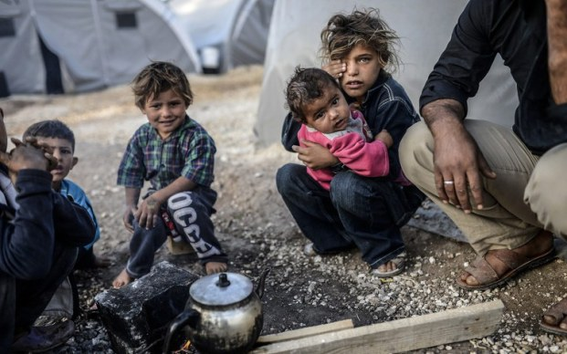 Kurdish children sit around a fire outside a tent in the Rojava refugee camp in Suruc, Sanliurfa province, near the besieged Syrian town of Kobane, also known as Ain al-Arab, on October 26, 2014. Turkey said on October 24 that hundreds of Syrian rebels are to reinforce Kurdish fighters defending the Syrian town of Kobane, as Washington voiced confidence that its fall to jihadists could be averted. Iraq's autonomous Kurdish region also plans to send reinforcements to Kobane, which has held off a relentless assault from the Islamic State (IS) group for more than five weeks. AFP PHOTO / BULENT KILIC (Photo credit should read BULENT KILIC/AFP/Getty Images)