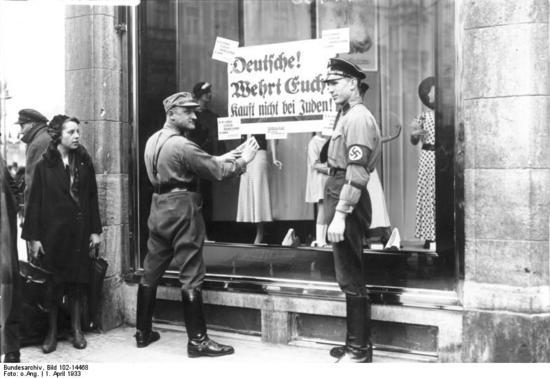 """An den Fenstern jüdischer Geschäfte werden von Nationalsozialisten Plakate mit der Aufforderung """"Deutsche, wehrt euch, kauft nicht bei Juden"""" angebracht."""